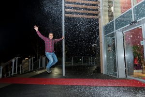 A man jumping for joy after planning the perfect Christmas party